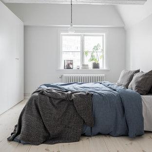 Inredning av ett minimalistiskt mellanstort sovrum, med vita väggar, ljust trägolv och beiget golv