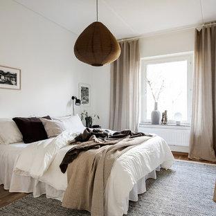 Idéer för ett skandinaviskt huvudsovrum, med vita väggar och mellanmörkt trägolv