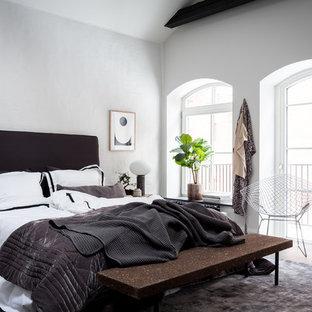 Idéer för att renovera ett mellanstort skandinaviskt sovrum, med vita väggar, mörkt trägolv och brunt golv