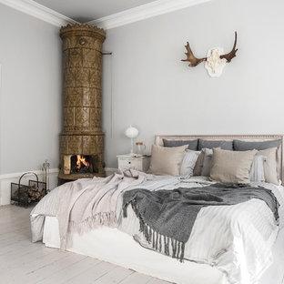 Idéer för mellanstora nordiska huvudsovrum, med målat trägolv, vitt golv, grå väggar och en öppen hörnspis