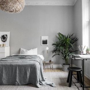 Inredning av ett minimalistiskt stort huvudsovrum, med grå väggar och ljust trägolv