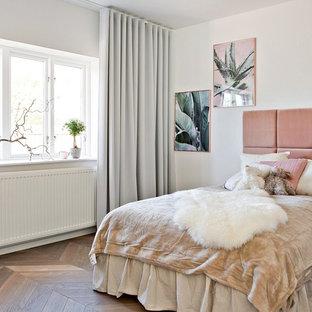 Foto på ett stort vintage sovrum, med vita väggar och mellanmörkt trägolv