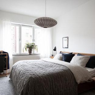 Foto på ett funkis sovrum, med vita väggar, mellanmörkt trägolv och brunt golv
