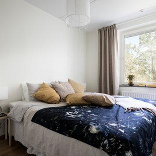 Idéer för att renovera ett mellanstort skandinaviskt huvudsovrum, med vita väggar, mellanmörkt trägolv och brunt golv