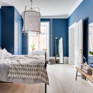 Immagine di una grande camera matrimoniale classica con pareti blu, parquet chiaro e nessun camino