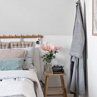 Bild på ett nordiskt sovrum, med vita väggar, ljust trägolv och beiget golv