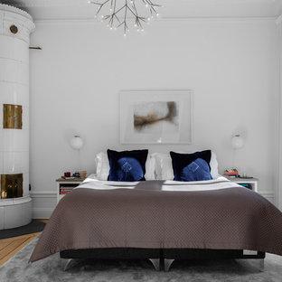 Foto de dormitorio principal, escandinavo, de tamaño medio, con paredes blancas, suelo de madera en tonos medios, estufa de leña, marco de chimenea de baldosas y/o azulejos y suelo beige