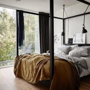 Idéer för ett mellanstort nordiskt sovrum, med vita väggar och ljust trägolv