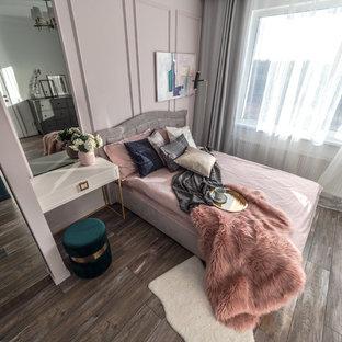 Esempio di una piccola camera matrimoniale classica con pareti rosa, pavimento in laminato e pavimento marrone