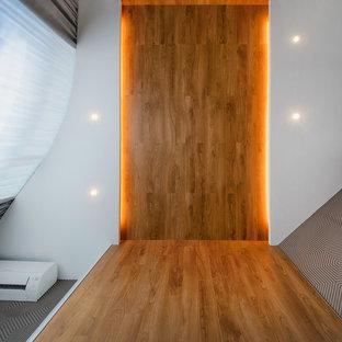 Ejemplo de dormitorio principal, actual, pequeño, con paredes blancas, suelo laminado y suelo marrón