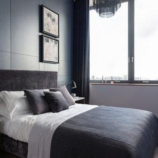 Contemporary bedroom in London with grey walls, medium hardwood flooring and brown floors.