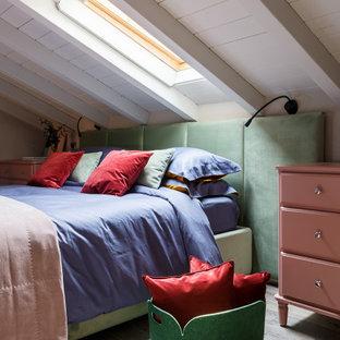 Small mediterranean loft-style bedroom in Milan with beige walls and medium hardwood floors.