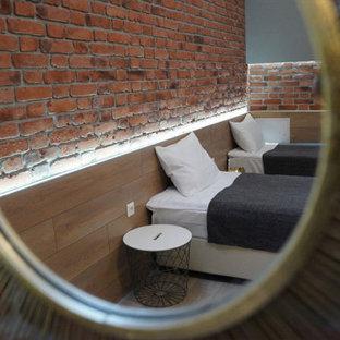Ejemplo de habitación de invitados industrial, de tamaño medio, sin chimenea, con paredes rojas, suelo de baldosas de porcelana, marco de chimenea de ladrillo y suelo beige