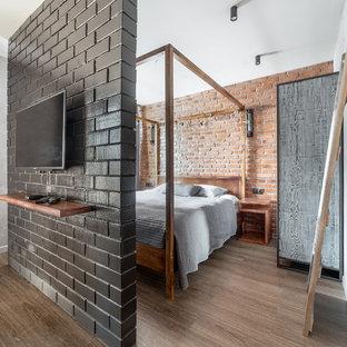 Стильный дизайн: спальня в стиле лофт с паркетным полом среднего тона, коричневым полом и серыми стенами - последний тренд
