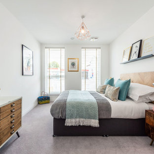 This is an example of a contemporary bedroom in London with white walls, carpet and grey floors.