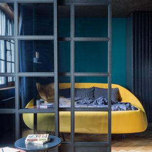 Modelo de dormitorio principal, industrial, de tamaño medio, sin chimenea, con paredes azules y suelo de madera en tonos medios