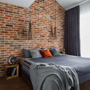 Пример оригинального дизайна: большая спальня в стиле лофт с красными стенами, темным паркетным полом, коричневым полом, сводчатым потолком и кирпичными стенами