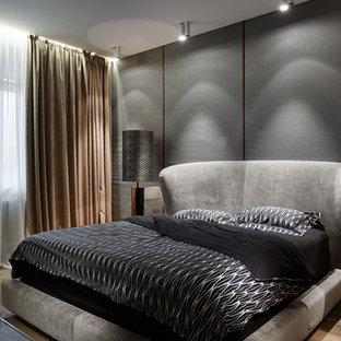 На фото: хозяйские спальни в современном стиле с серыми стенами, паркетным полом среднего тона и коричневым полом