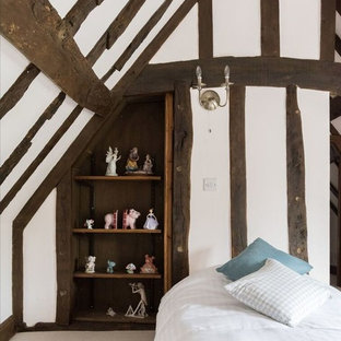 Design ideas for a small rustic bedroom in London with white walls, carpet and beige floors.