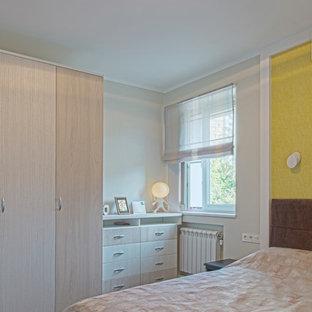 モスクワの中サイズのコンテンポラリースタイルのおしゃれな主寝室 (黄色い壁、ラミネートの床、茶色い床) のレイアウト