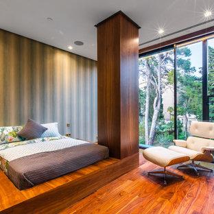 На фото: спальня в современном стиле с зелеными стенами, темным паркетным полом и коричневым полом с