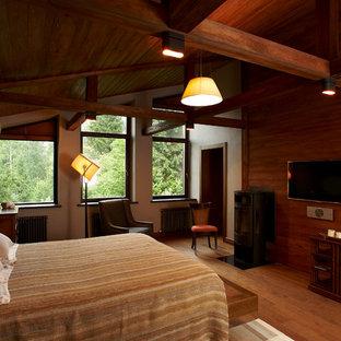 Foto de dormitorio principal, actual, de tamaño medio, con paredes grises, suelo de madera pintada, estufa de leña, marco de chimenea de metal y suelo marrón