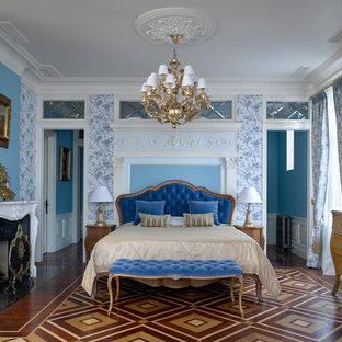 Пример оригинального дизайна: хозяйская спальня в классическом стиле с синими стенами, стандартным камином и разноцветным полом