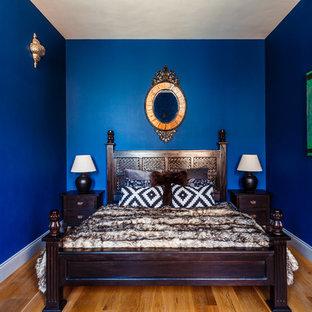 Esempio di una camera matrimoniale boho chic di medie dimensioni con pareti blu, nessun camino e pavimento in legno massello medio