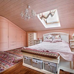 На фото: спальня в стиле кантри с розовыми стенами, паркетным полом среднего тона и коричневым полом с