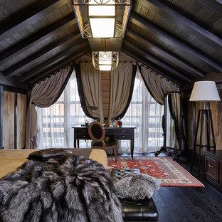 На фото: хозяйская спальня в стиле кантри с темным паркетным полом, черным полом, коричневыми стенами и правильным освещением с