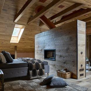 На фото: хозяйские спальни в стиле кантри с коричневыми стенами, паркетным полом среднего тона, двусторонним камином и фасадом камина из плитки