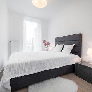 Kleines Skandinavisches Hauptschlafzimmer ohne Kamin mit weißer Wandfarbe und hellem Holzboden in Moskau