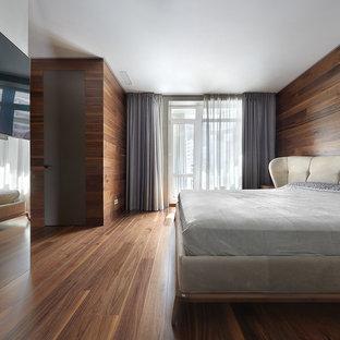 Стильный дизайн: большая хозяйская спальня в современном стиле с коричневыми стенами, паркетным полом среднего тона и коричневым полом - последний тренд