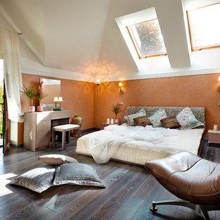 Foto de dormitorio principal, actual, de tamaño medio, sin chimenea, con parades naranjas y suelo de madera oscura