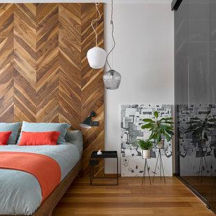 На фото: хозяйские спальни среднего размера в современном стиле с серыми стенами, деревянным полом и коричневым полом