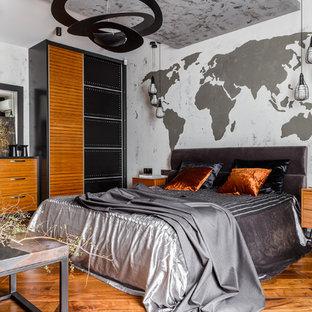 На фото: хозяйская спальня среднего размера в стиле лофт с серыми стенами, паркетным полом среднего тона и коричневым полом