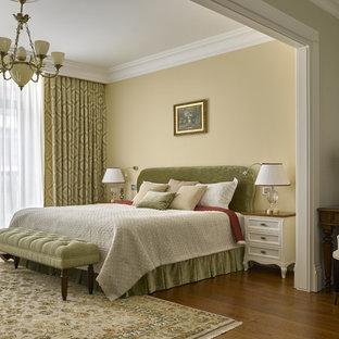 Foto de dormitorio principal, clásico, con paredes amarillas y suelo de madera en tonos medios