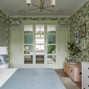 Photo of a tropical master bedroom in Moscow with green walls, medium hardwood floors and brown floor.