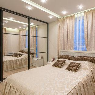 Diseño de dormitorio principal, clásico, de tamaño medio, con paredes blancas y suelo laminado