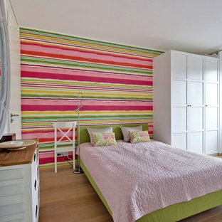Immagine di una camera degli ospiti boho chic con pavimento in legno massello medio e pavimento marrone