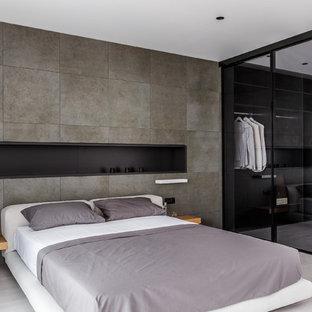 Пример оригинального дизайна: хозяйская спальня в современном стиле с серыми стенами и серым полом без камина