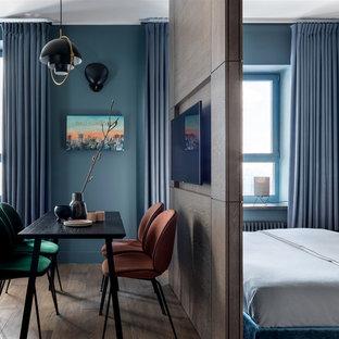 Ejemplo de dormitorio principal, actual, pequeño, con suelo de madera en tonos medios, suelo marrón y paredes azules
