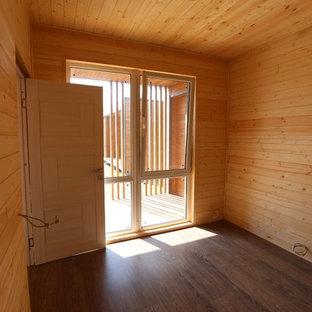 Ejemplo de habitación de invitados minimalista, pequeña, con paredes blancas, suelo laminado y suelo marrón