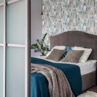 Стильный дизайн: хозяйская спальня среднего размера в современном стиле с серыми стенами, коричневым полом и обоями на стенах - последний тренд