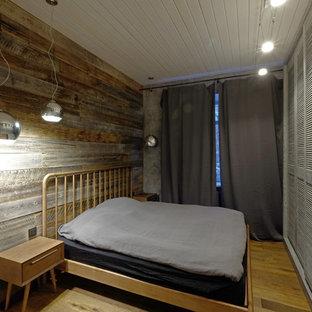 Diseño de dormitorio principal, urbano, pequeño, sin chimenea, con paredes grises, suelo de madera en tonos medios y suelo naranja