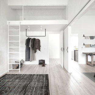 Photo of a small industrial guest bedroom in Saint Petersburg with white walls, painted wood floors and beige floor.