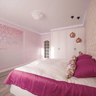 Modelo de dormitorio principal, tradicional renovado, de tamaño medio, con paredes rosas, suelo laminado y suelo gris