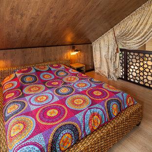 Ispirazione per una piccola camera da letto stile loft etnica con parquet chiaro e nessun camino