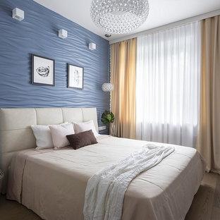 Idee per una camera matrimoniale design con pareti blu, pavimento in legno massello medio e pavimento marrone