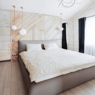 Modelo de dormitorio principal, contemporáneo, pequeño, con paredes beige, suelo de madera en tonos medios y suelo azul